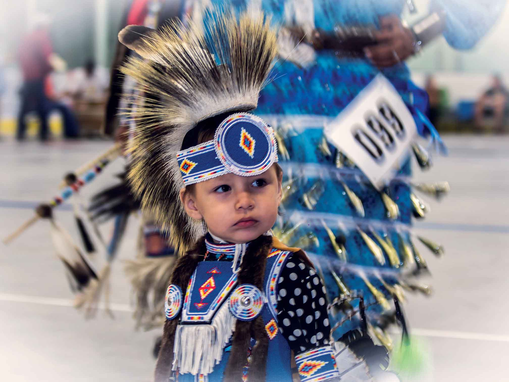 A child in traditional garb watches a powwow