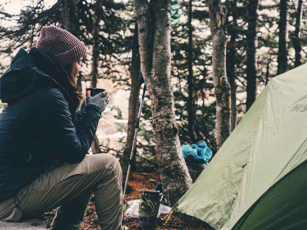 A woman sits outside of a tent sipping coffee wearing a toque and lots of layers. When preparing your camping checklist, make sure you bring lots of layers!