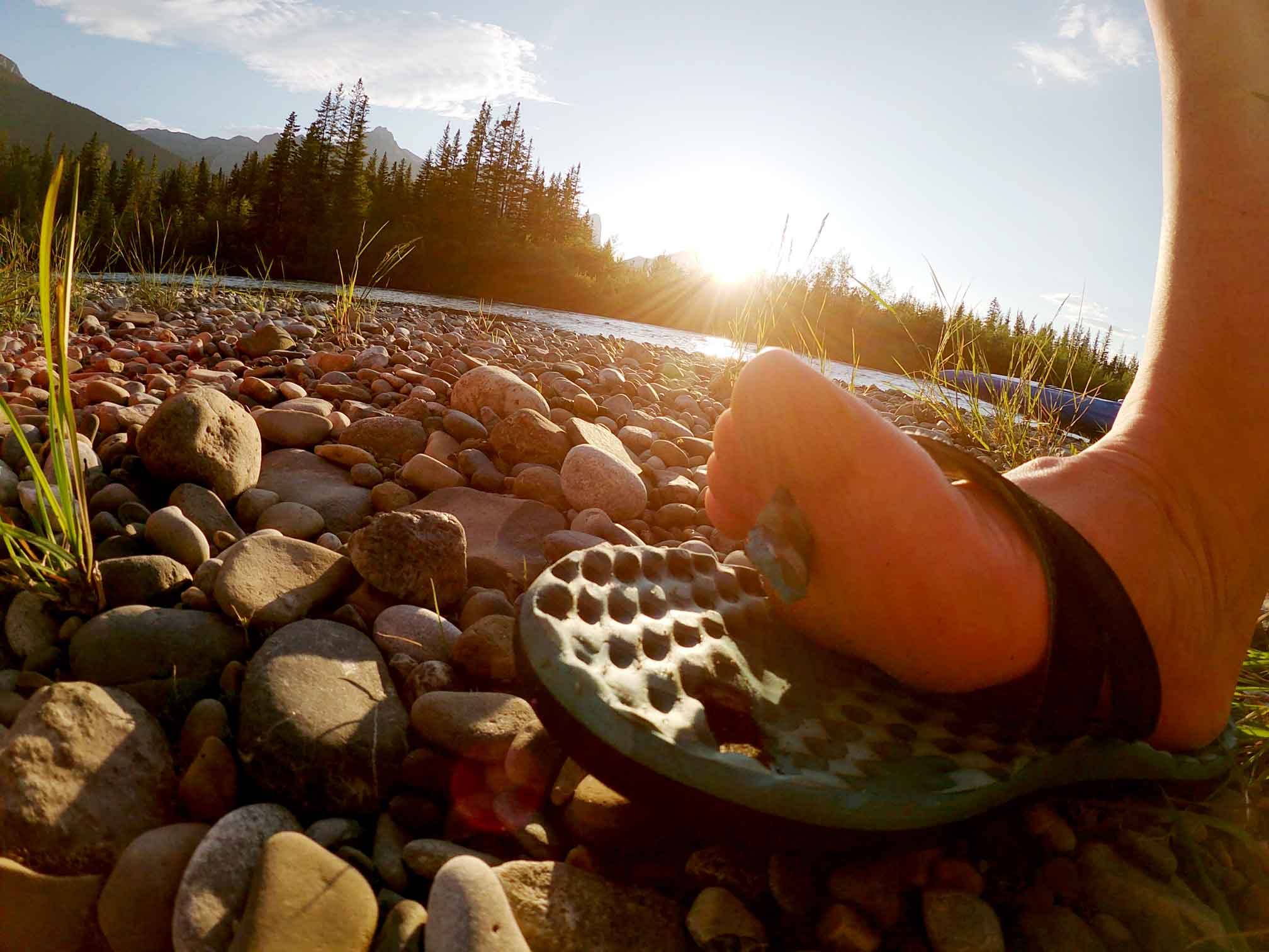 A broken flip flop on the rocks after a portage canoeing in Canmore during an evening paddle from Canmore to Exshaw