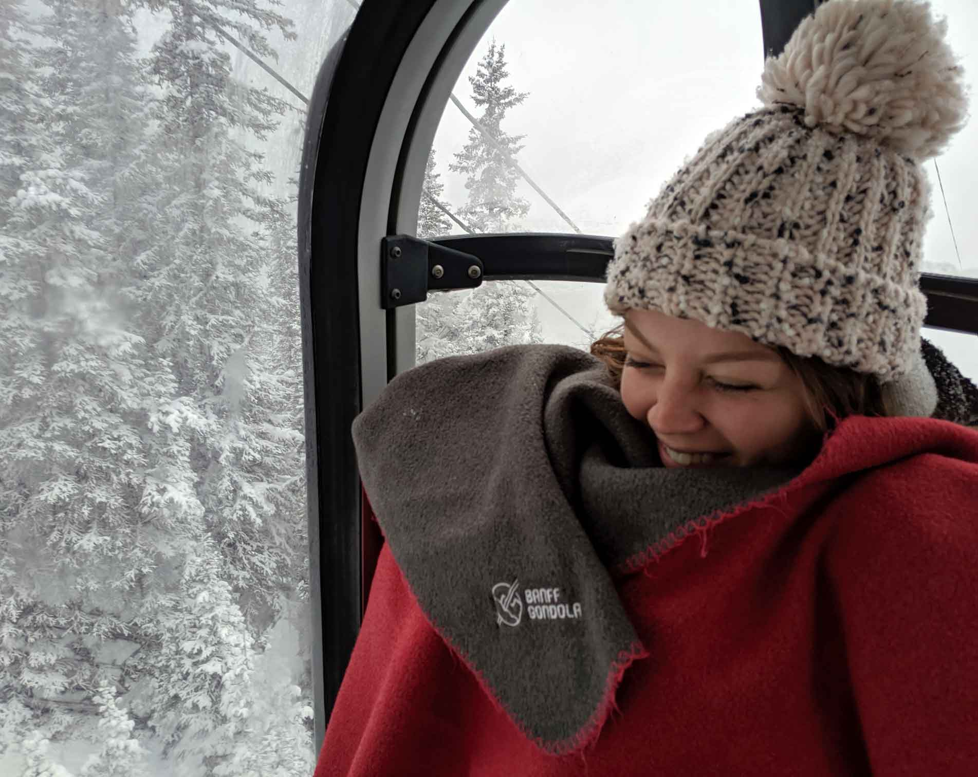 I'm sitting on the Banff Gondola, bundled in a Pursuit blanket with snow covered trees behind me.