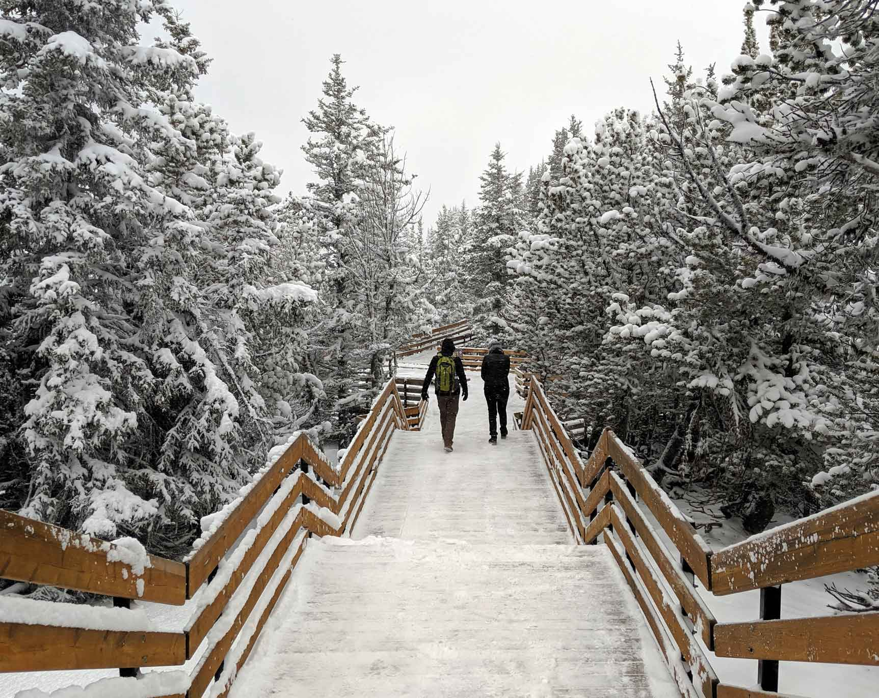 Two people walk along the snowy boardwalk at the top of the Banff Gondola
