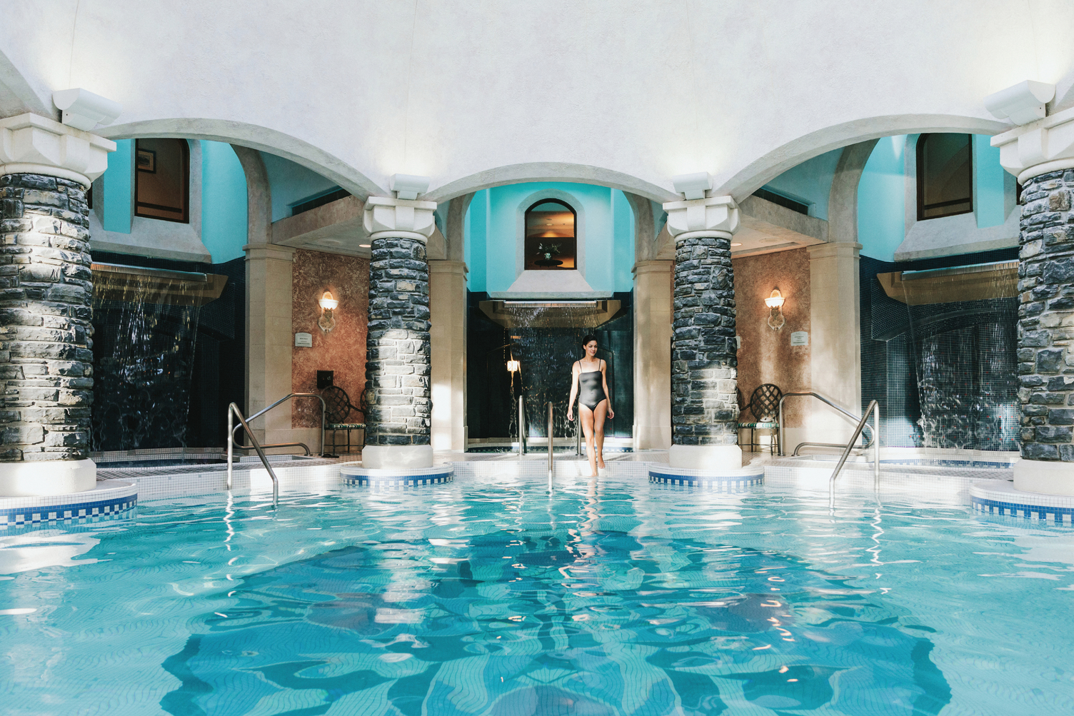 A woman walks into the mineral pool at the Fairmont Banff Springs