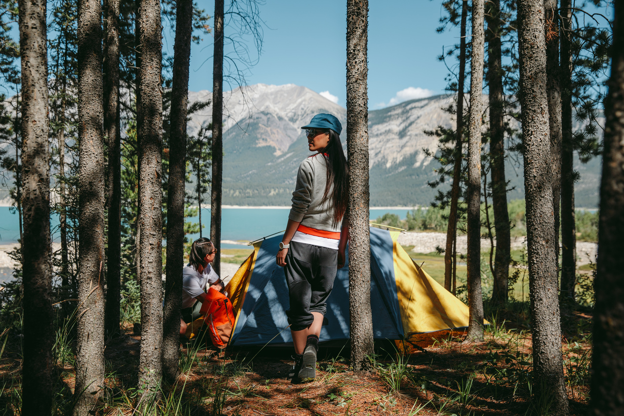 Two people at a tent campsite overlooking the river and mountains in Jasper National Park