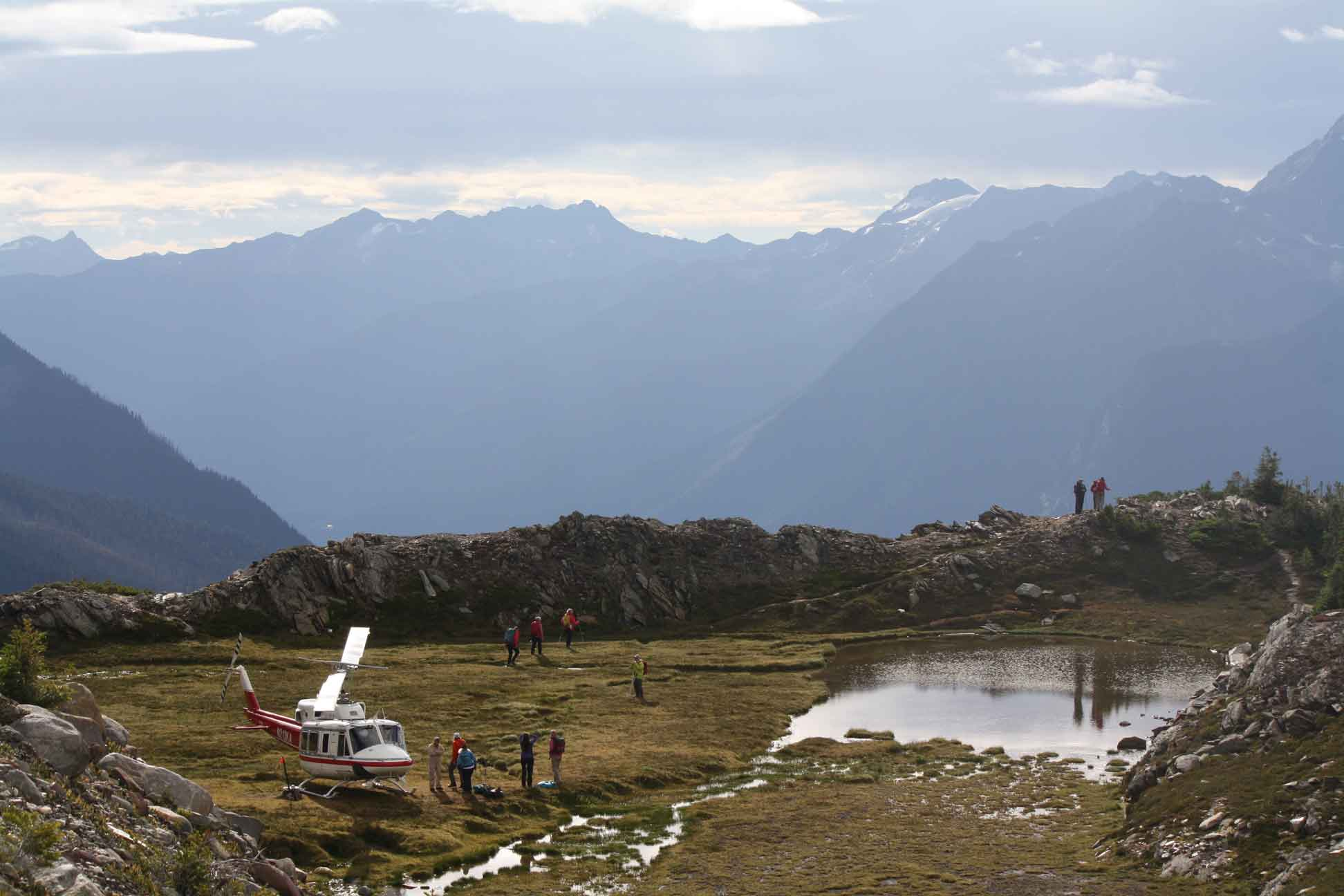People exit a helicopter by a glacier lake with mountain scenery off the beaten path with CMH