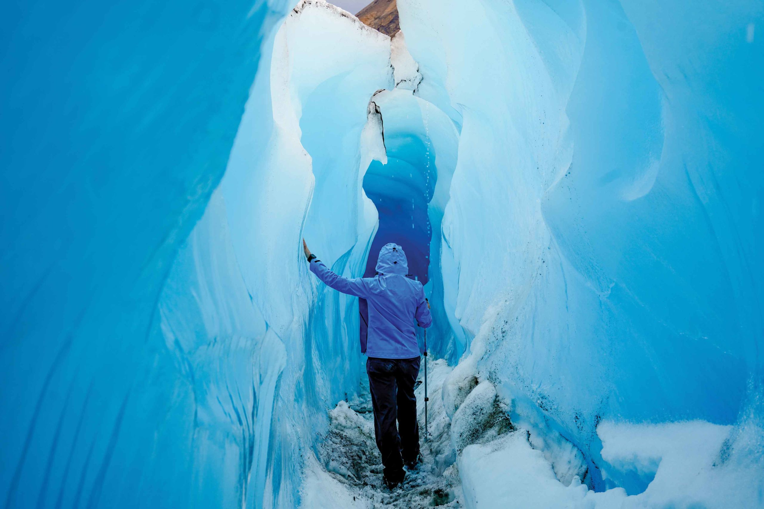 People walk through a crevasse in the glacial ice on a tour with Rockaboo Mountain Adventures