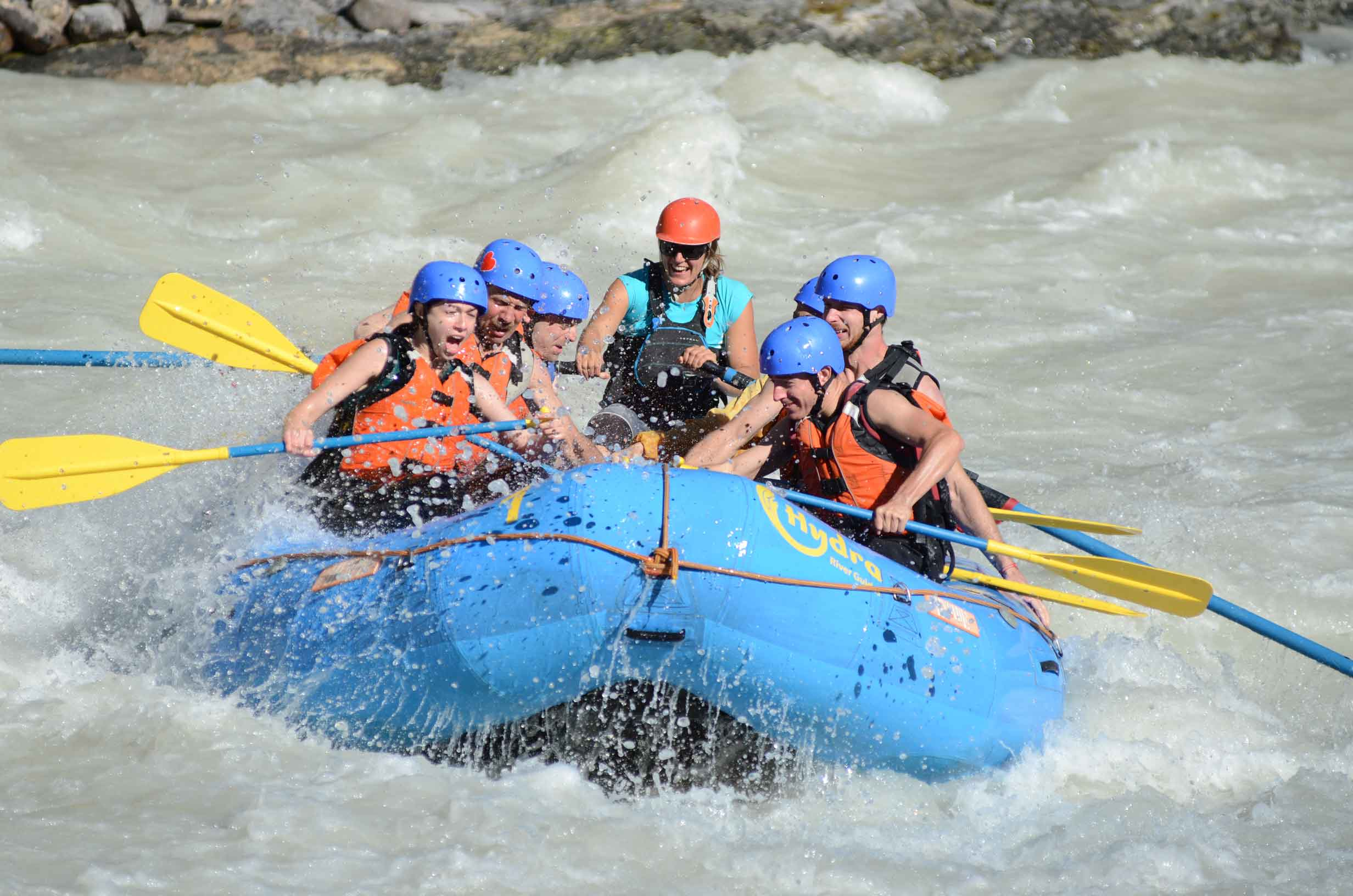 A blue raft crashes through whitewater