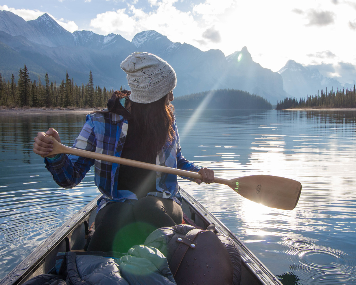 A woman is dressed for a day on the water in a canoe in Jasper