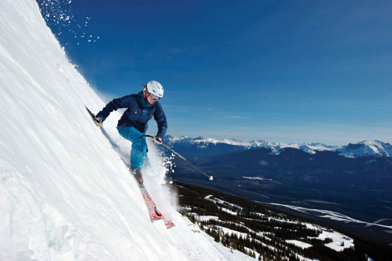 A woman on alpine skis on a very steep slope. Shop local for ski tuning this winter.