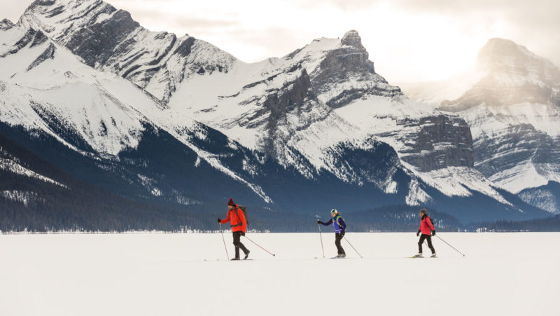 Three people enjoy Nordic ski season in front of mountains