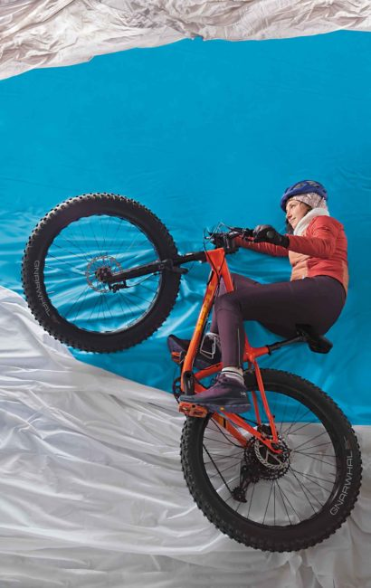A woman on a fat bike on a blue and white background