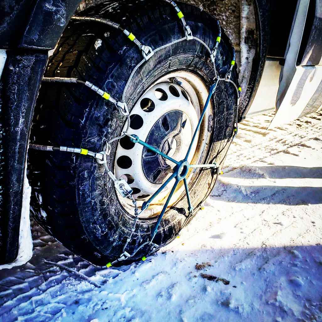Close up of a tire with snow chains from the Snowcat Snowshoe Adventure with White Mountain Adventures