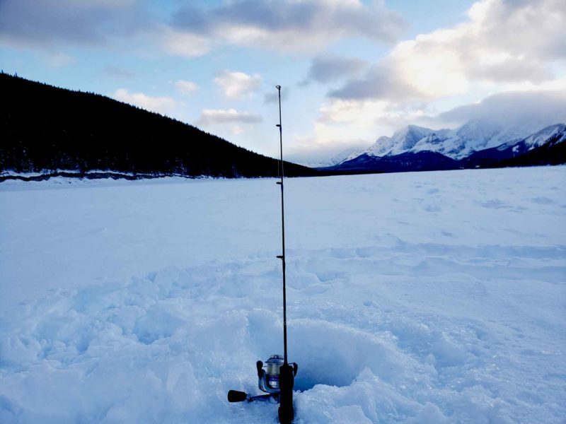 An ice fishing pole in front of mountain scenery on a winter adventure