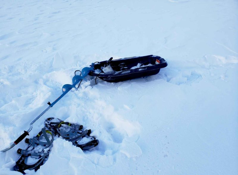 snowshoes, fishing pole and a sled on a winter adventure