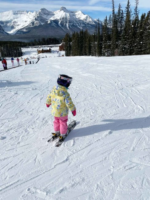 A 4 year old child skiing on her own after a ski lesson at Lake Louise Ski Resort