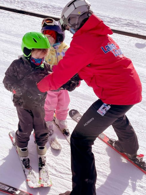 Jessica catches the kids as they learn to glide during their ski lesson at Lake Louise Ski Resort