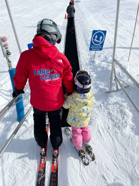 Jessica helping Cadence up the magic carpet during a ski lesson at Lake Louise Ski Resort