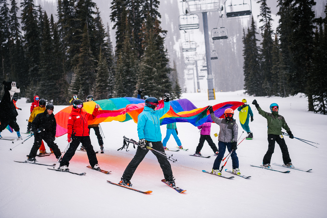 Skiers at Marmot Basin with a rainbow flag for Jasper Pride