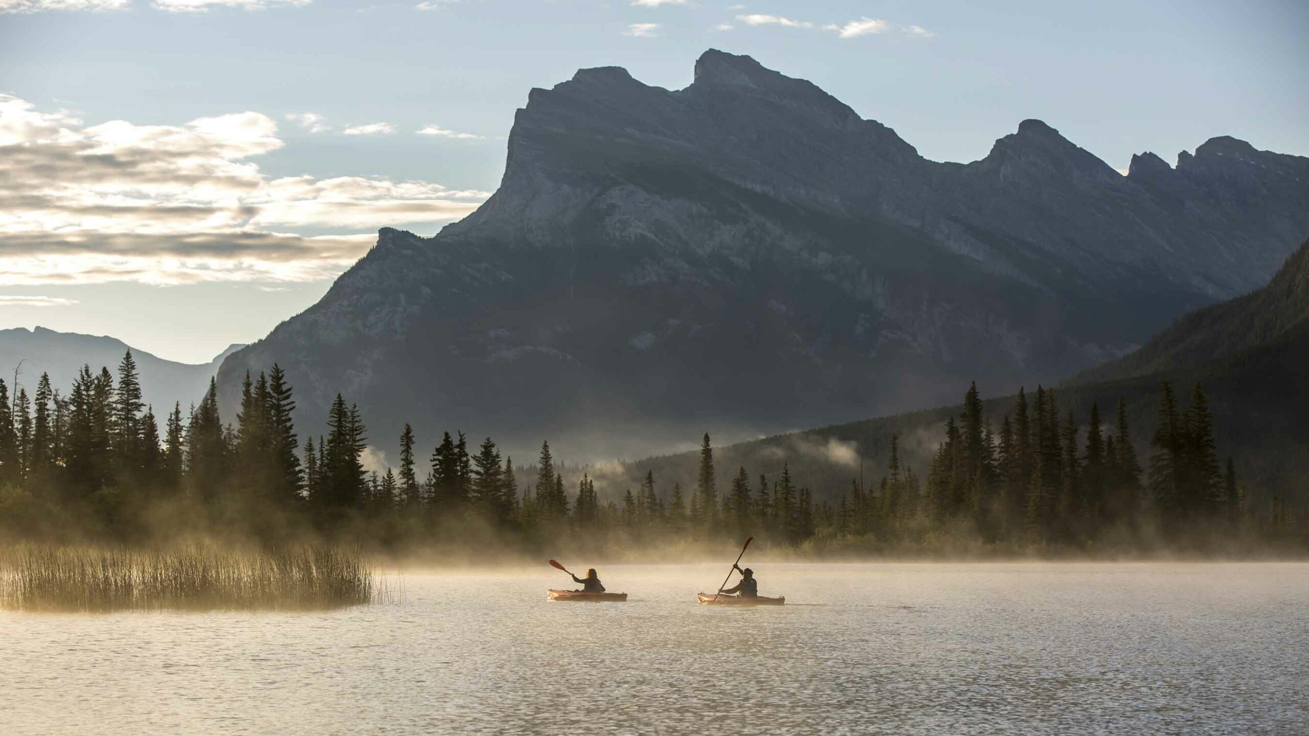 Two people kayak on Vermillion Lakes under Mount Rundle in Banff during summer in the Canadian Rockies