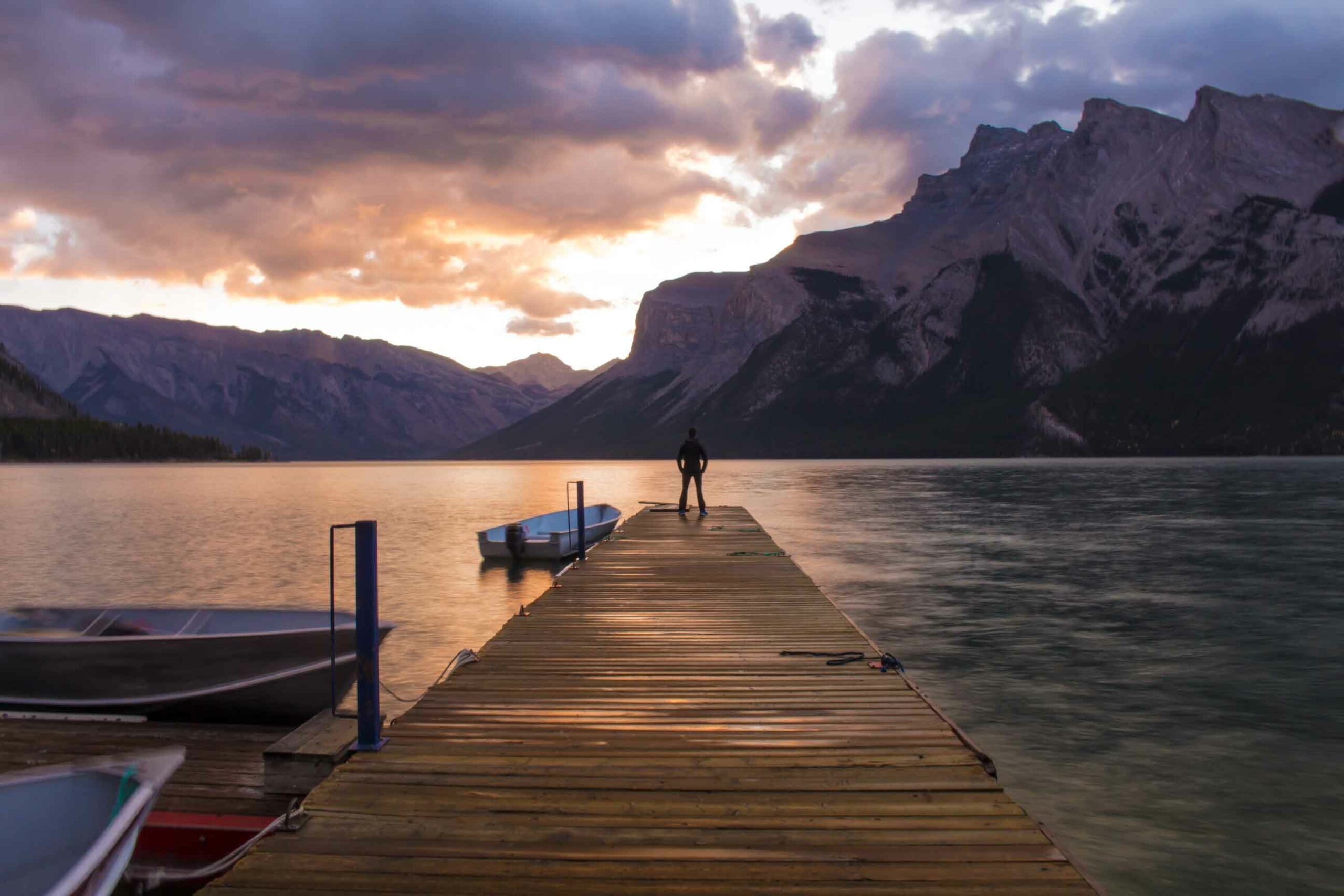 A person stands at the end of a wood dock at sunset on Lake Minnewanka in Banff during summer in the Canadian Rockies