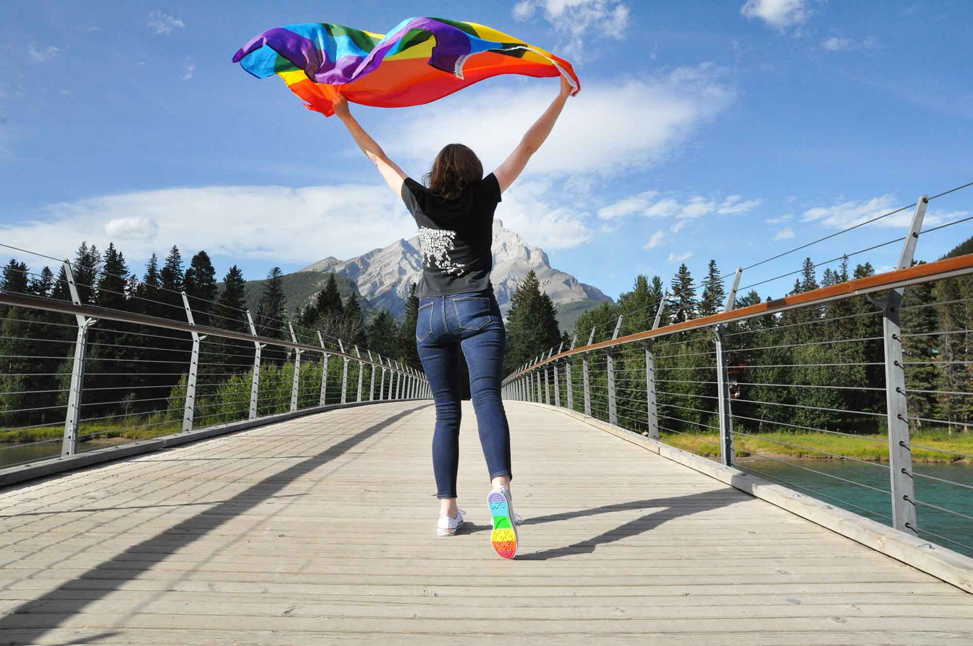 A person with a rainbow flag and rainbow shoes on the Banff Pedestrian Bridge for Banff Pride